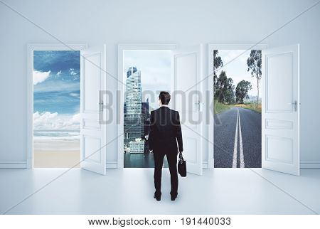 Back view of young businessman in concrete interior with three open doors and different views. Urbanization concept. 3D Rendering