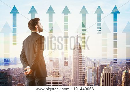 Back view of young businessman looking at city with upward chart arrows. Growth concept