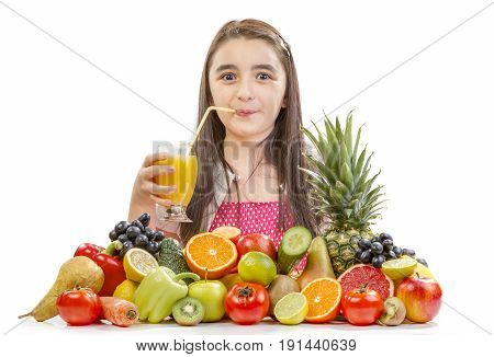 Little girl drinking orange juice. Happy girl with fruits assortment on the table.