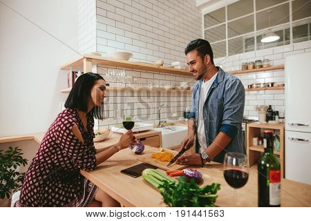 Young Couple Talking While Cooking In Kitchen