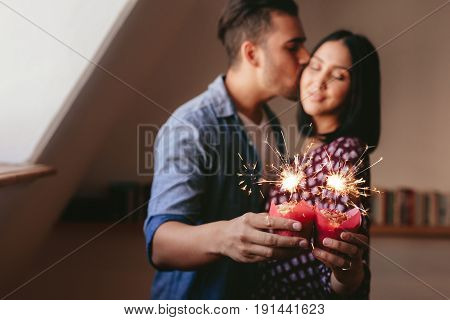 Sparklers On Cupcakes In Hand Of Couple