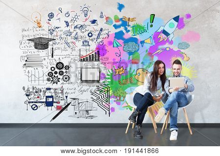 Young man and woman using tablet on concrete room with creative sketch on wall. Left and right brain sides