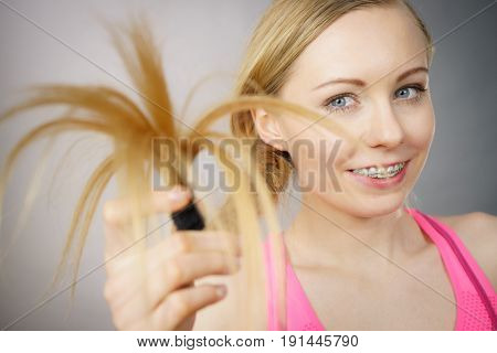 Happy Woman Looking At Her Hair Ends