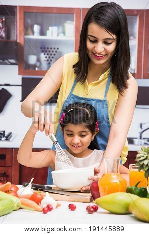 Pretty Indian young lady or mother with cute girl child or  daughter in kitchen having fun time with table full of fresh vegetables and fruits