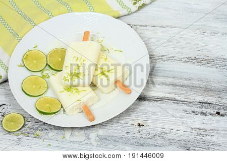 Homemade lime ice lolly from cream with coconut. Delicious fruit popsicle with the stick on wooden table