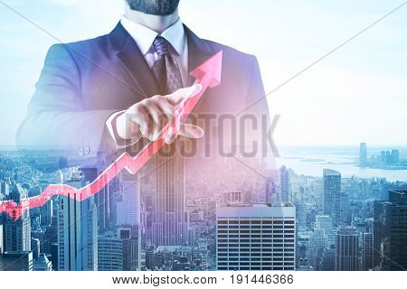 Abstract image of businessman pointing at upward red chart arrow on city background. Financial growth concept. Double exposure