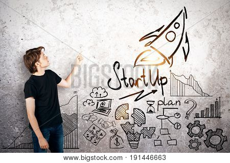 Side view of young businessman pointing at concrete wall with rocket sketch. Start up concept