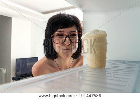 Woman sees ice cream in the fridge