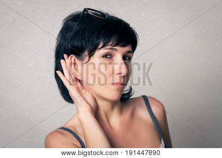 Woman close up making the listening sign