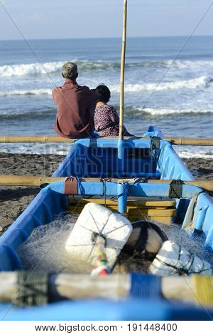 Yuong fisherman sit together with her father in a boat