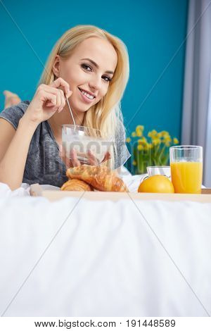 Pretty young blonde woman enjoying a breakfast of fresh crisp croissant and coffee in bed