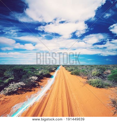 Blue streak of light on dirt road against cloudy sky