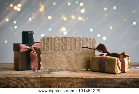 Fathers Day card gift box with brown ribbon perfume bottle paper tag on wooden table gray background blurred light effect