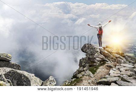 Tourist on the top of a mountain peak. The traveler celebrates the ascent to the mountain peak. Freedom - the concept.