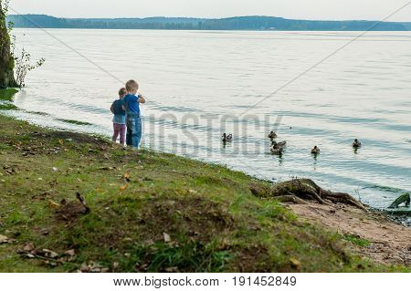 Two adorable sisters feeding ducks by a river at summer