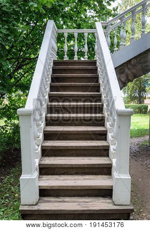 White wooden staircase of gazebo-pavilion in old park