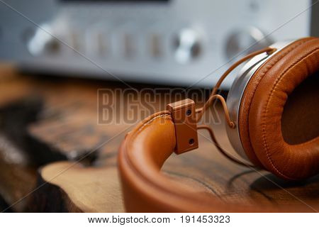 Vintage Headphones lie on a wooden table. Background amplifier hifi