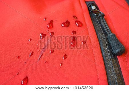 large water rain drops on red waterproof weatherproof clothes like coat or jacket. closeup macro shot of buckles zipper pocket fastener