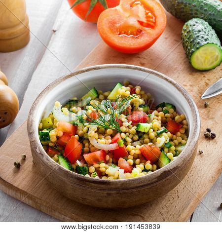 Delicious Israeli couscous Ptitim with vegetables on a white wooden table. Cooking of healthy vegetarian food for the meal. Traditional Moroccan cuisine. Top view shot.
