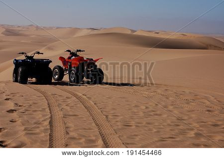 Red and Blue Dune Buggies waiting for their riders; revving for the next race across the dunes of the Kalahari Desert