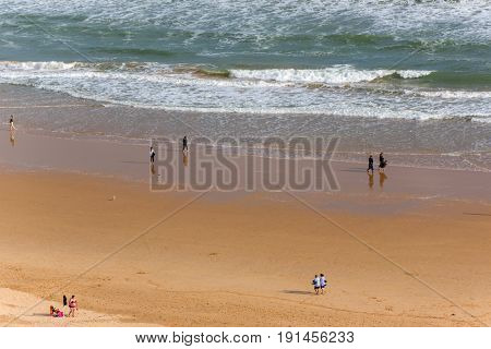 PRAIA DA ROCHA, PORTUGAL - APRIL 22, 2017: People at the famous beach of Praia da Rocha in Portimao. This beach is a part of famous tourist region of Algarve.