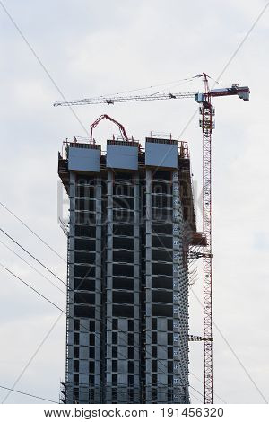 Construction site of modern high-rise building. Lift tower crane and new residential building under construction against blue sky. Vertical