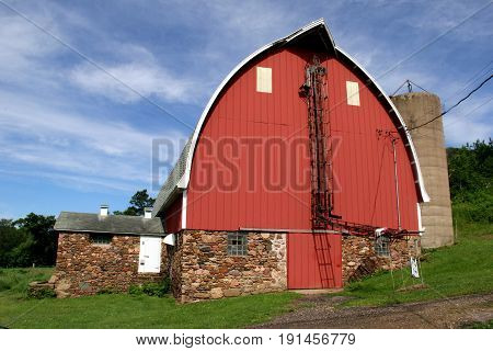 Vintage red barn with field stone foundation on a green grass yard and wooded background