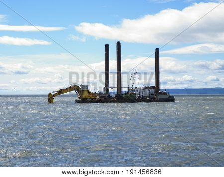 Barge With Excavator. Excavator On The Barge. Special Vessel With A Ladle And Piles For Anchoring On