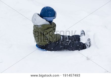 little boy in the winter riding with a snow hill