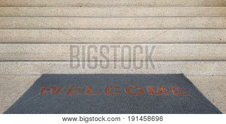 Welcome mat on a brick flooring by front staircase,Welcome carpet on floor