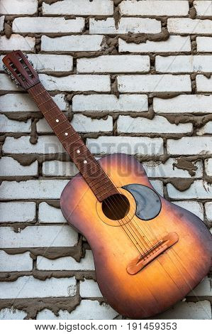 Acoustic guitar resting against a white  brick background with copy space