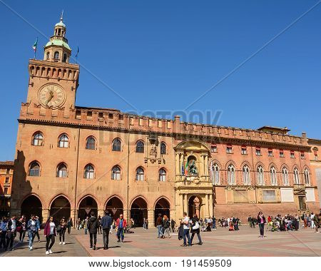 Bologna Italy - April 22 2017: Palace of Accursio in Piazza Maggiore of Bologna with tourists on a sunny day