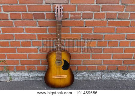 Acoustic guitar resting against a red brick wall with copy space