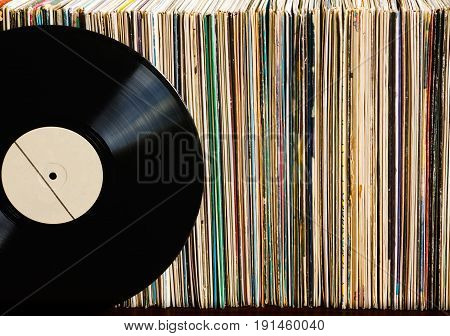 Vinyl record with copy space in front of a collection of albums, vintage process