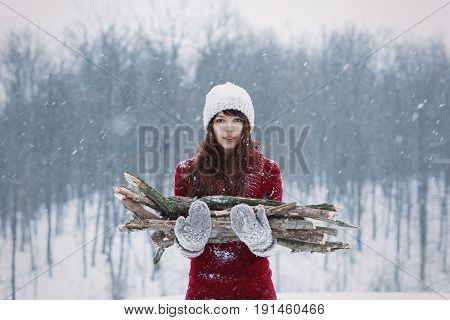 Beautiful frozen girl holding firewoods on walk through winter snow forest. Girl with mittend and firewood. Warm and firewoods in snow cold winter.