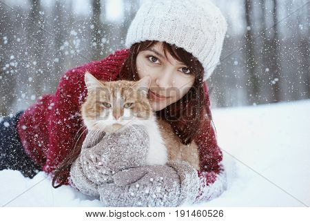 Beautiful girl with in red sweater and hat holding and playing with little fluffy cat in winter snowy park.