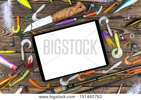 Fishing rod tackles and fishing baits reel on wooden board background with tablet computer isolated white screen empty space for text