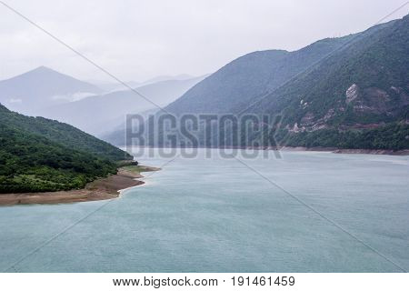 The picturesque lake in mountains, a reservoir in the mountain gorge between green hills, cloudy weather, an outdoor recreation