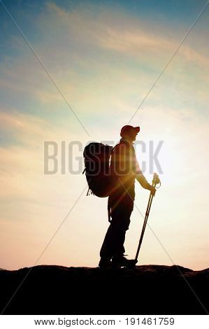 Hiker In Windcheater, Baseball Cap And With Trekking Poles Stand On Mountain Peak Rock.