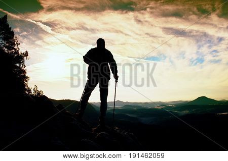 Silhouette Of Alone Hiker With Poles In Hand. Tourist With Sporty Backpack Stand On Rocky View Point