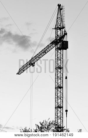 Old High-rise crane used in the construction of a multi-storey building in black and white photo