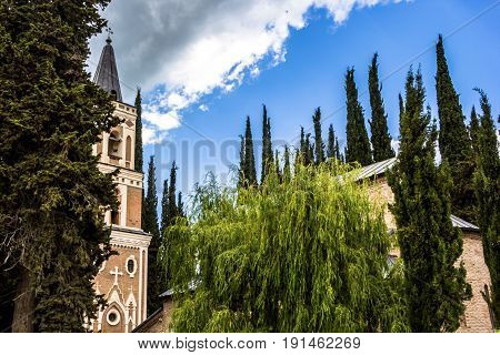 The beautiful Christian temple against green trees of cypresses, architecture of Georgia