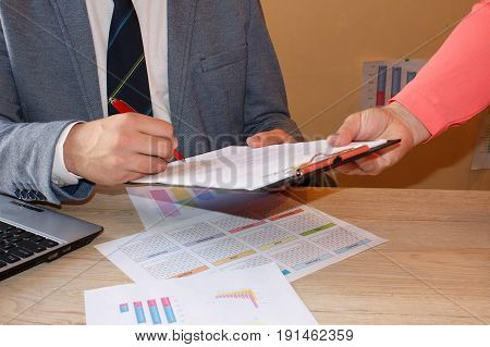 Conceptual image of a man signing a last will and testament document. Colleagues working together in office