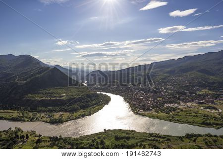 Beautiful view of the picturesque valley, merge of two rivers between green hills, a sunny weather, the nature and sights of Georgia