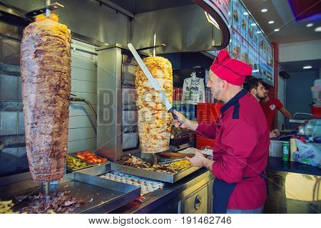 ISTANBUL TURKEY - MAY 4 2017: A chef is slicing traditional Turkish food Doner Kebab in a street food shop