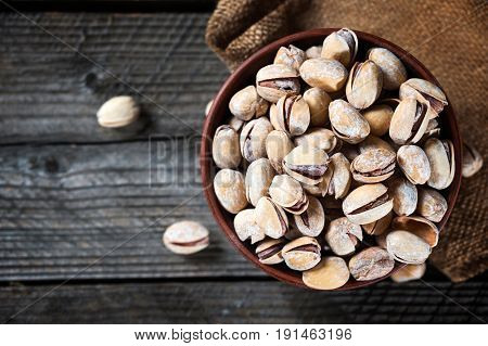Salted Roasted Pistachios Nuts In Broun Small Bowl Over Old Rustyc Wooden Textured Background.