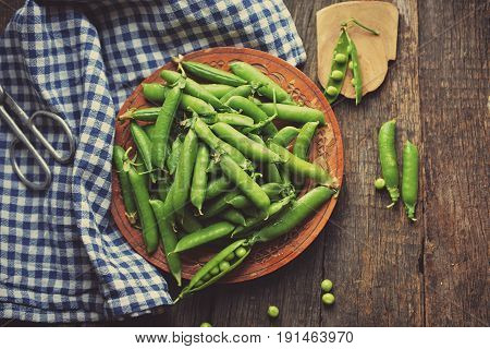 Young peas in a wooden plate on a wooden table. Standing next to a plate of pea pods. next to the plates is the stalk of peas.