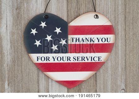 Retro USA flag on a heart shape wood sign on weathered wood