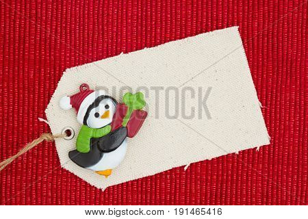 A cloth gift tag with a Christmas penguin on shiny red material that is blank for your message