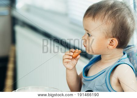 The Child Greedily Eating The Sausage